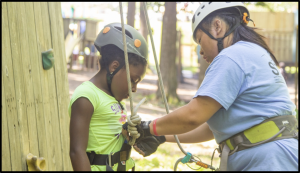 young girl putting on climbing helmet